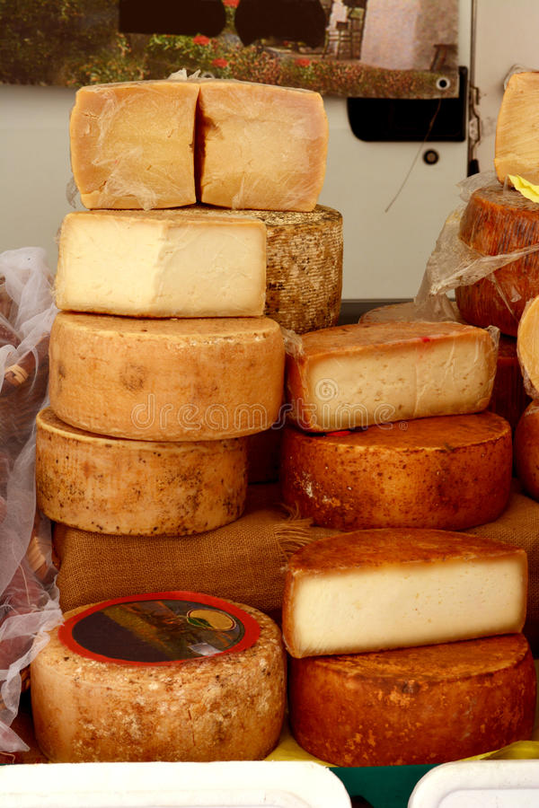 Cheese for sale on market. Heaps of various delicious fresh cheese wheels at an Italian market stand royalty free stock images
