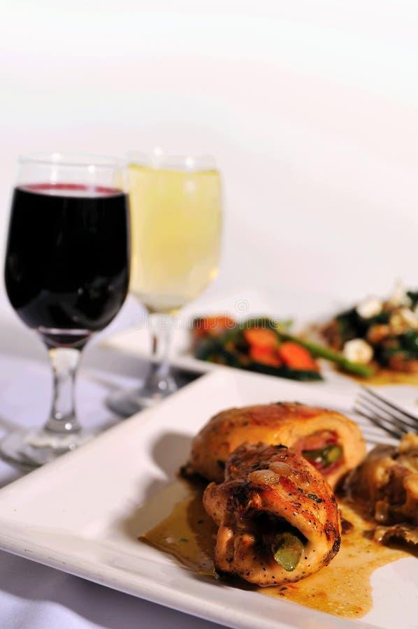 Italian chicken dinner with wine. Italian gourmet chicken dinner with glasses of wine in the background stock photo