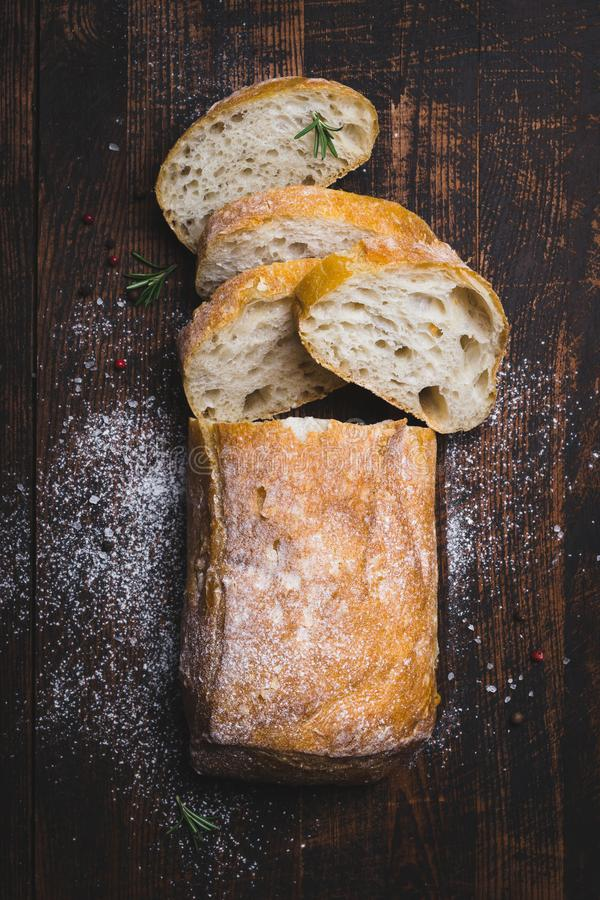 Italian ciabatta bread cut in slices on dark wooden background royalty free stock images