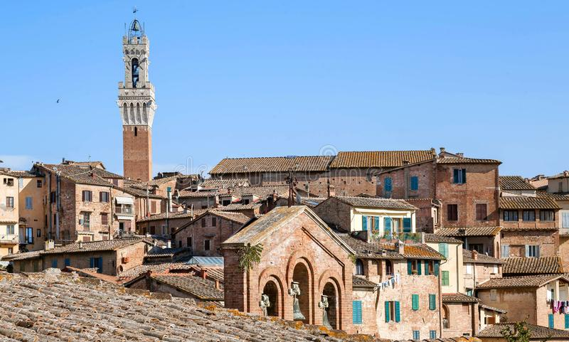 Italian city with brick houses and towers of Siena, Tuscany. Tile roofs and brick structures in Italy.  stock image