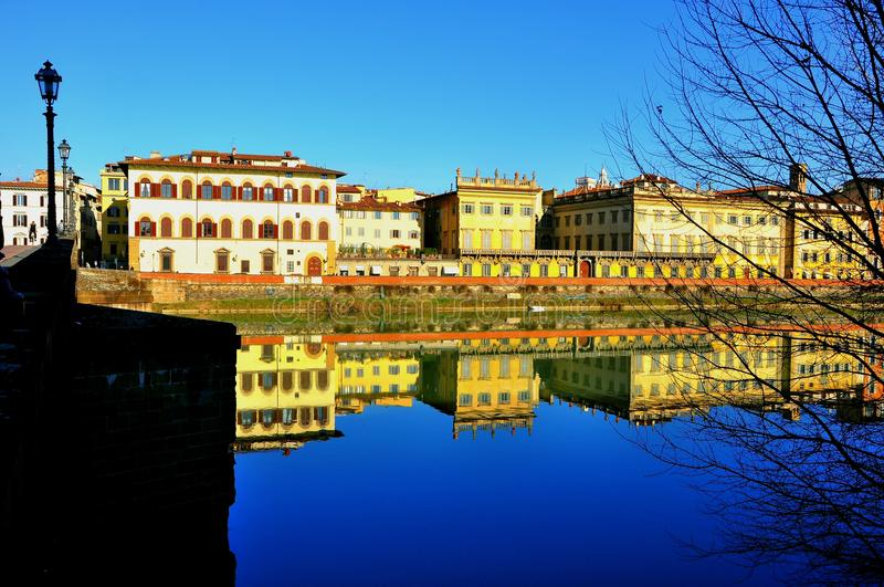 Italian city landscape. Buildings and bridges mirror in the river Arno in Florence, Italy. Urban cityscape stock photography