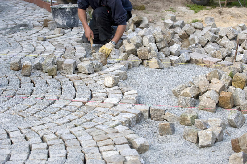 Italian cobblestone paver. An italian cobblestone paver during his work. Image taken outside with the worker on the ground. He is putting the stones in a stock image