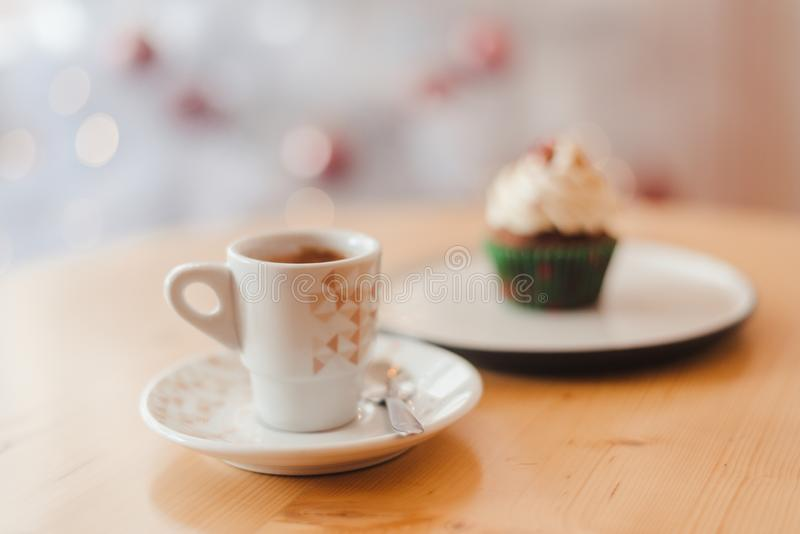 Italian coffee Cup and cupcake on the table near the Christmas tree with white bokeh. Italian coffee Cup and cupcake on the table near the white Christmas tree royalty free stock photos