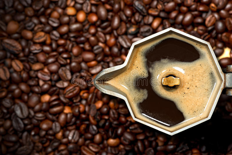 Italian Coffee Maker with Coffee Beans. Closeup of an old italian coffee maker moka pot - top view with roasted coffee beans on background royalty free stock image