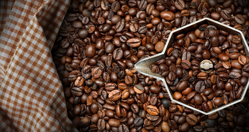 Italian Coffee Maker with Coffee Beans. Closeup of an old italian coffee maker moka pot - top view with roasted coffee beans inside and on background royalty free stock image