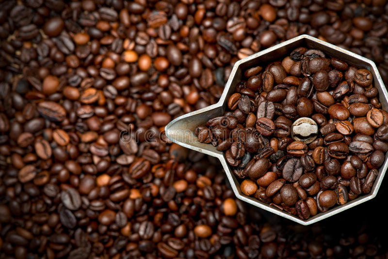 Italian Coffee Maker with Coffee Beans. Closeup of an old italian coffee maker moka pot - top view with roasted coffee beans inside and on background royalty free stock images