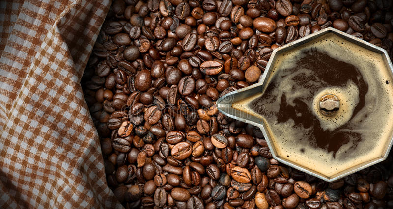 Italian Coffee Maker with Coffee Beans. Old italian coffee maker moka pot - top view with roasted coffee beans on the background with a checkered tablecloth royalty free stock images