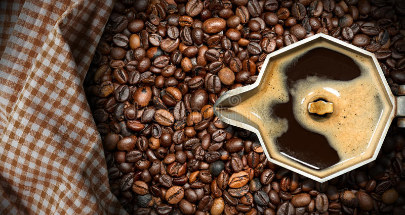 Italian Coffee Maker with Coffee Beans. Old italian coffee maker moka pot - top view with roasted coffee beans on the background with a checkered tablecloth stock photo