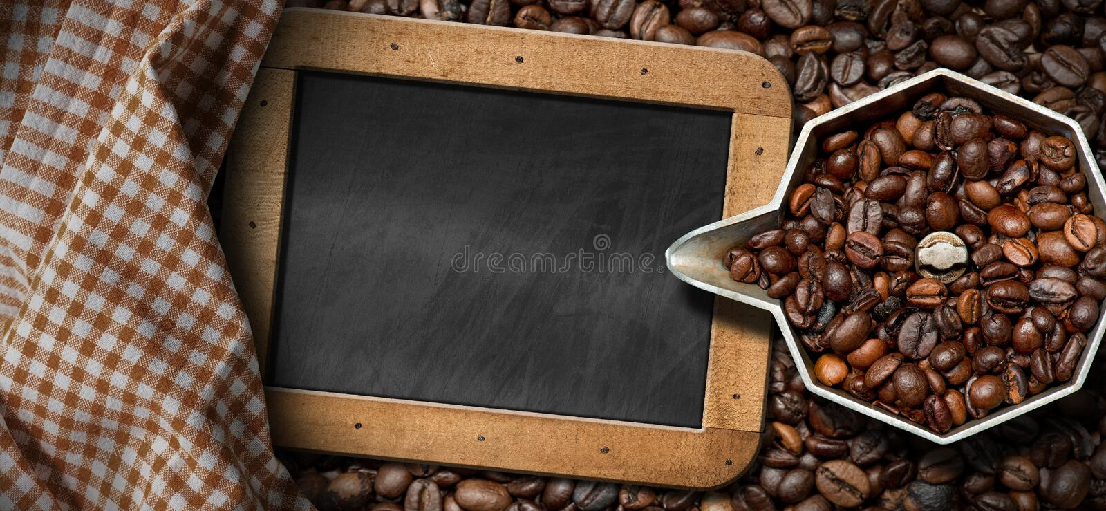 Italian Coffee Maker with Coffee Beans. Old italian coffee maker moka pot - top view with roasted coffee beans and an empty blackboard with copy space royalty free stock images