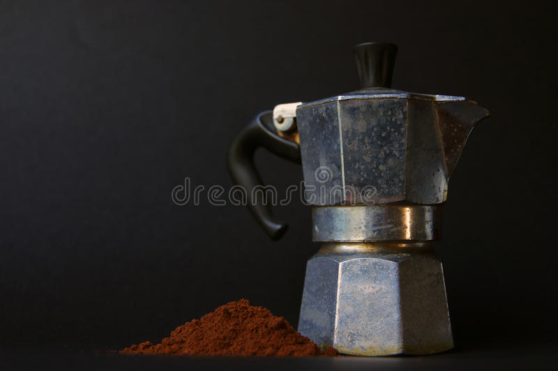 Italian coffee maker I. Italianl coffee maker with some coffee powder. They represent the fundamental ingredients for making a traditional coffee royalty free stock images