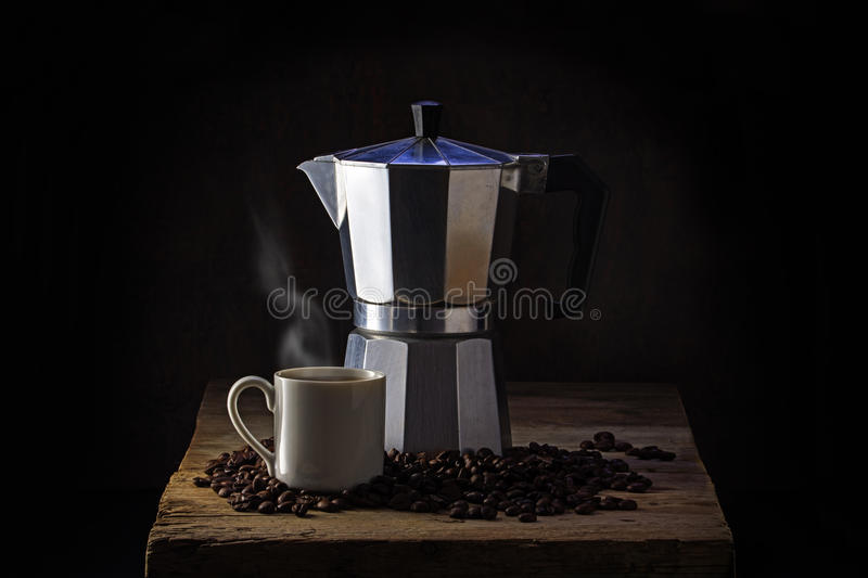 Italian coffee maker, steaming cup and whole coffee beans on rustic wood, dark background, copy space on each side royalty free stock photos
