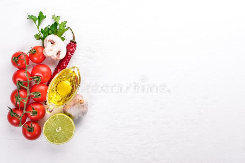Italian cooking, fresh vegetables, cherry tomatoes. On a white wooden background. Top view. Copy space stock photography