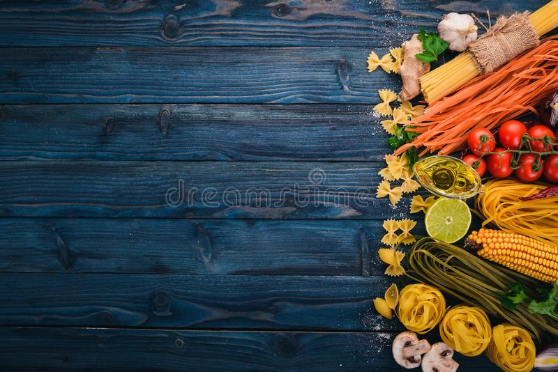 Italian Cooking, Fresh Vegetables. Set of pasta, noodles, spaghetti. On a blue wooden background. Top view. Copy space stock photos