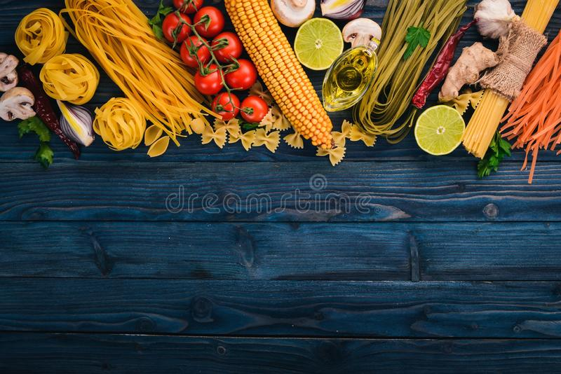 Italian Cooking, Fresh Vegetables. Set of pasta, noodles, spaghetti. On a blue wooden background. Top view. Copy space royalty free stock image