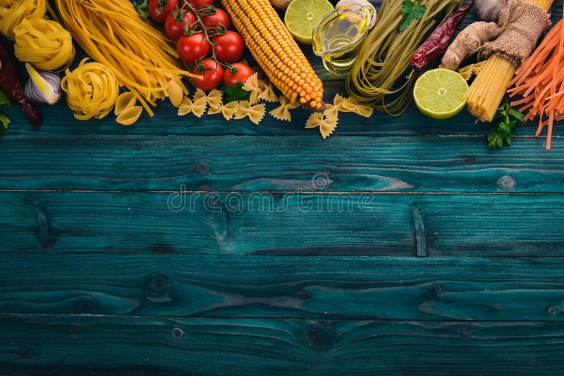 Italian Cooking, Fresh Vegetables. Set of pasta, noodles, spaghetti. On a blue wooden background. Top view. Copy space stock photography