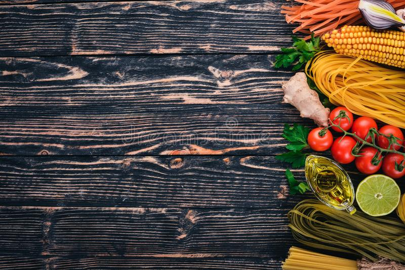 Italian cooking, fresh vegetables and spices. Set of pasta, noodles, spaghetti. On a dark wooden background. royalty free stock photos