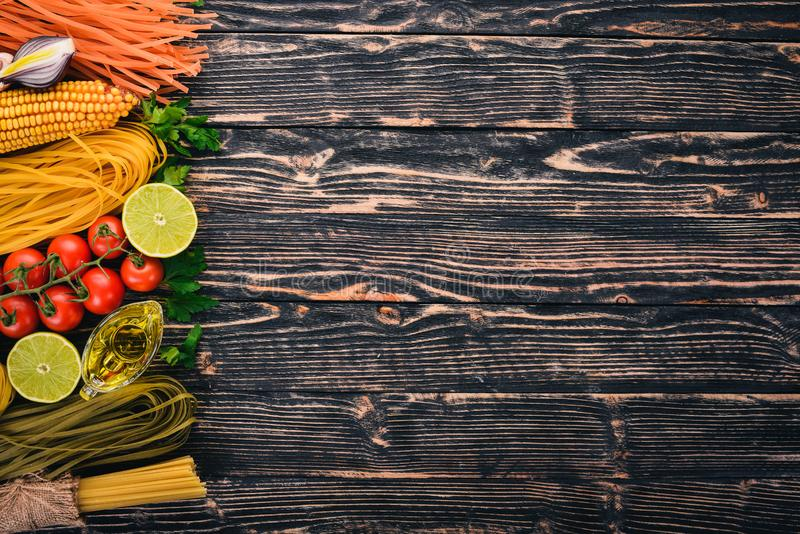 Italian cooking, fresh vegetables and spices. Set of pasta, noodles, spaghetti. On a dark wooden background. Top view. Copy space stock photos