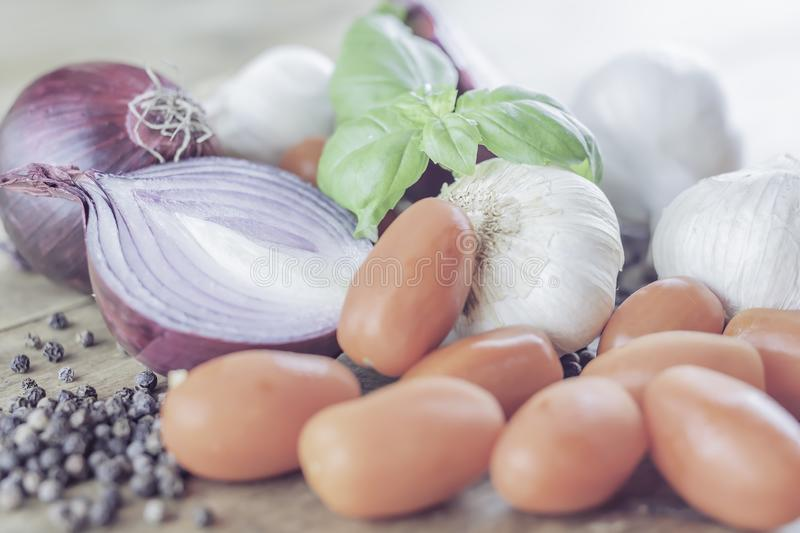 Italian cooking ingredients placed on rustic wooden table. Italian cooking ingredients.Mixed organic vegetables placed on rustic wooden background.Red onion royalty free stock photography