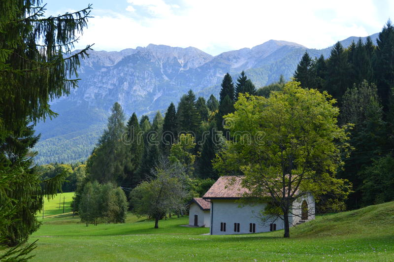 Italian countryside home and Dolomite mountains. In pastoral northeastern Italy a country home sits with a backdrop of the forested Dolomite mountains stock photo