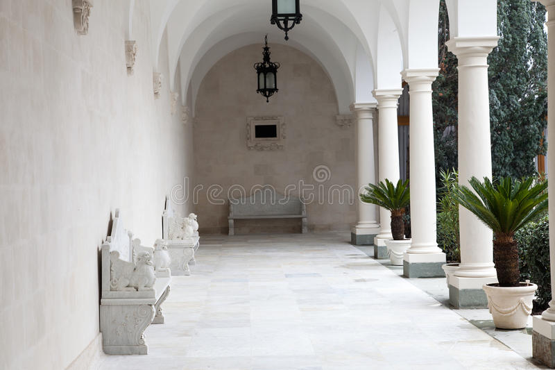 Italian court with piazza, stone benches and palm trees