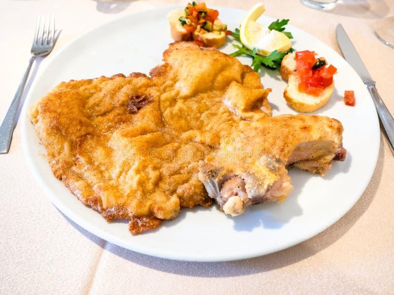 Italian cuisine - Cotoletta alla Milanese on plate stock images