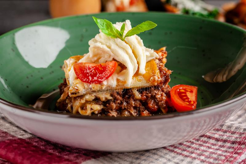Italian cuisine. Lasagna with minced meat bolognese. With suluguni cheese and cherry tomatoes. Serving dishes in a restaurant royalty free stock image