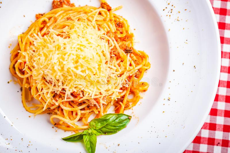 Italian cuisine. Spaghetti bolognese with meat, parmesan cheese and tomatoes on white plate. Top view. Close up royalty free stock images