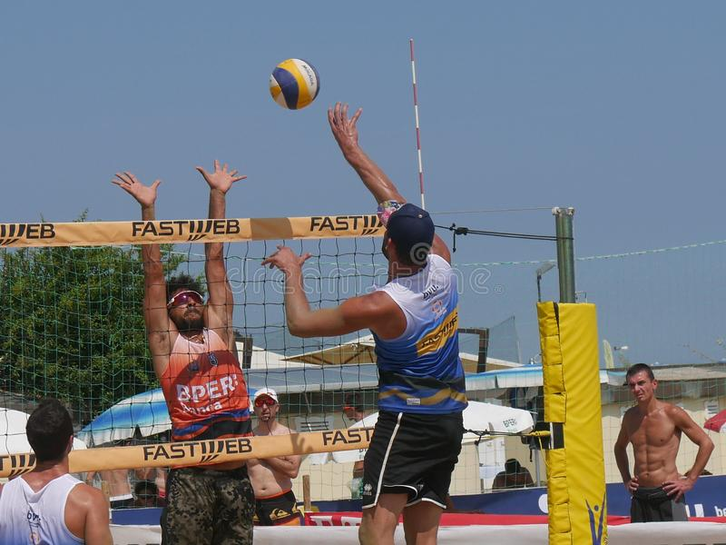 Italian Cup Beach Volley 2018 - Men Qualification. Male athletes playing in qualification Beach Volley match - FIPAV Beach Volley Italian Championship 2018 stock image