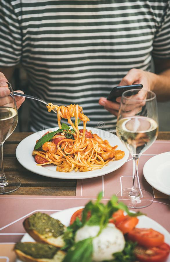 Italian dinner at bistrot with caprese and pasta with shrimps royalty free stock photo