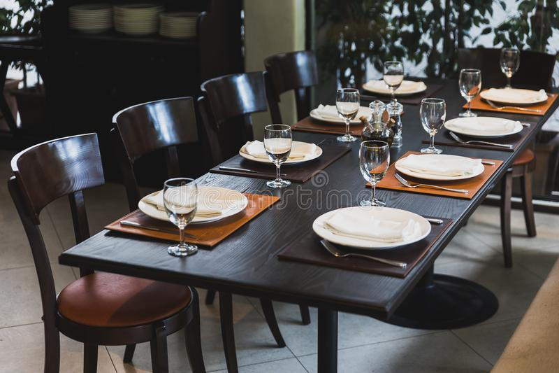 Italian dinner table for eight with cutleries, plates, glasses, napkins and naperies on the table. stock photo