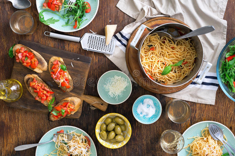 Italian dinner table with pasta, appetizers and white wine. Top view royalty free stock photo