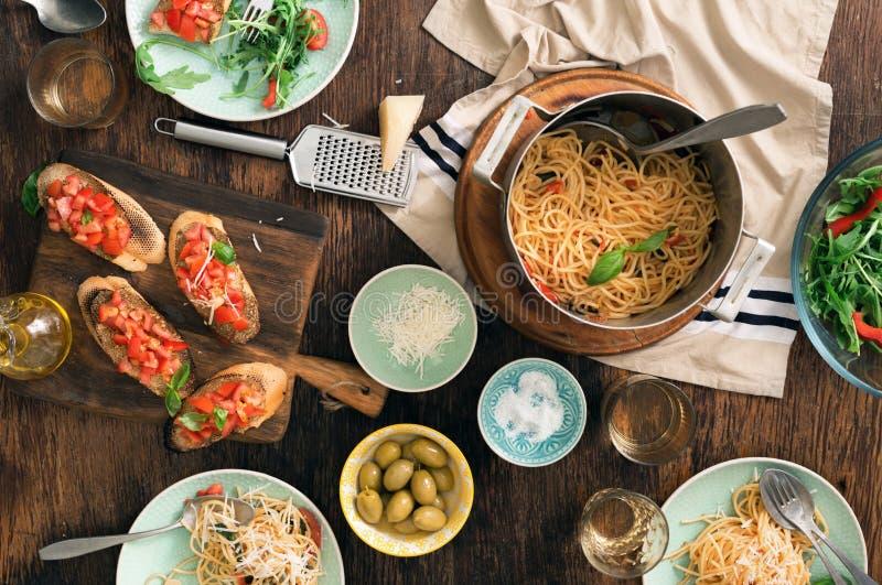 Italian dinner table with pasta, bruschetta and salad royalty free stock photos