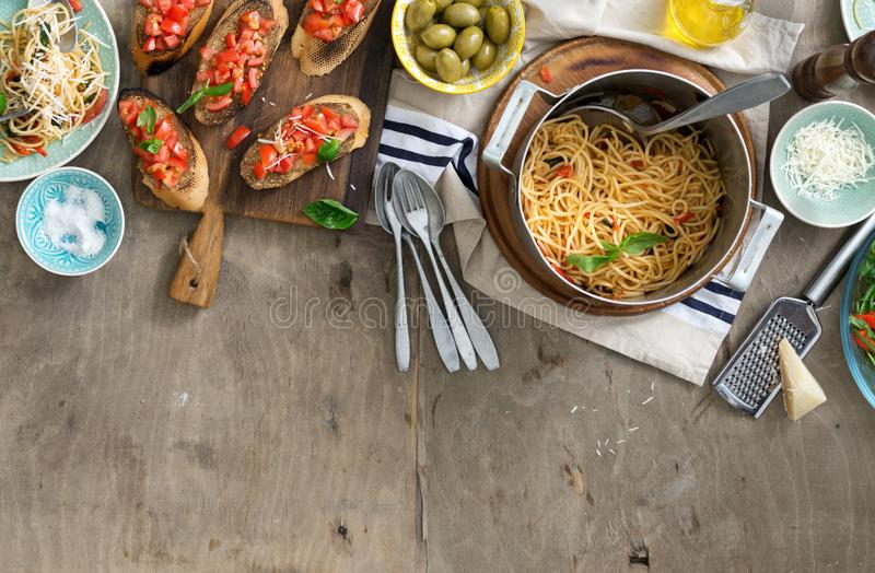 Italian dinner table with pasta and bruschetta on wooden table royalty free stock photo