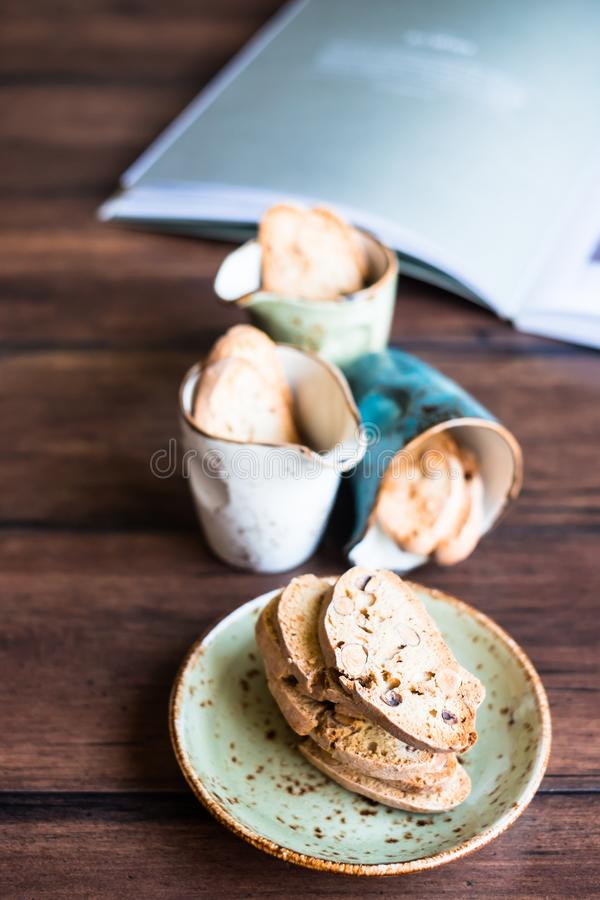 Italian dry cookies cantucci or biscotti with almond nuts stacked on a dessert plate on a wooden table, selective focus. Image wit royalty free stock image