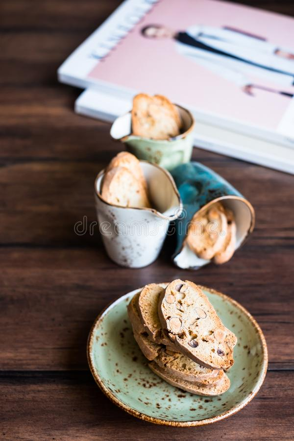 Italian dry cookies cantucci or biscotti with almond nuts stacked on a dessert plate on a wooden table, selective focus. Image wit royalty free stock photography