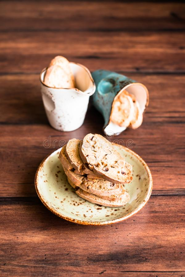 Italian dry cookies cantucci or biscotti with almond nuts stacked on a dessert plate on a wooden table, selective focus. Image wit royalty free stock images