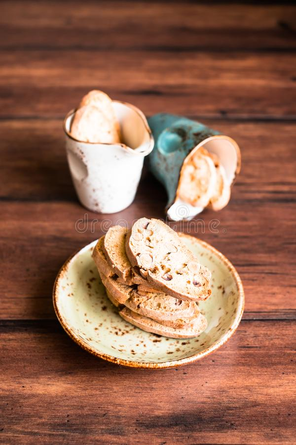 Italian dry cookies cantucci or biscotti with almond nuts stacked on a dessert plate on a wooden table, selective focus. Image wit royalty free stock photos