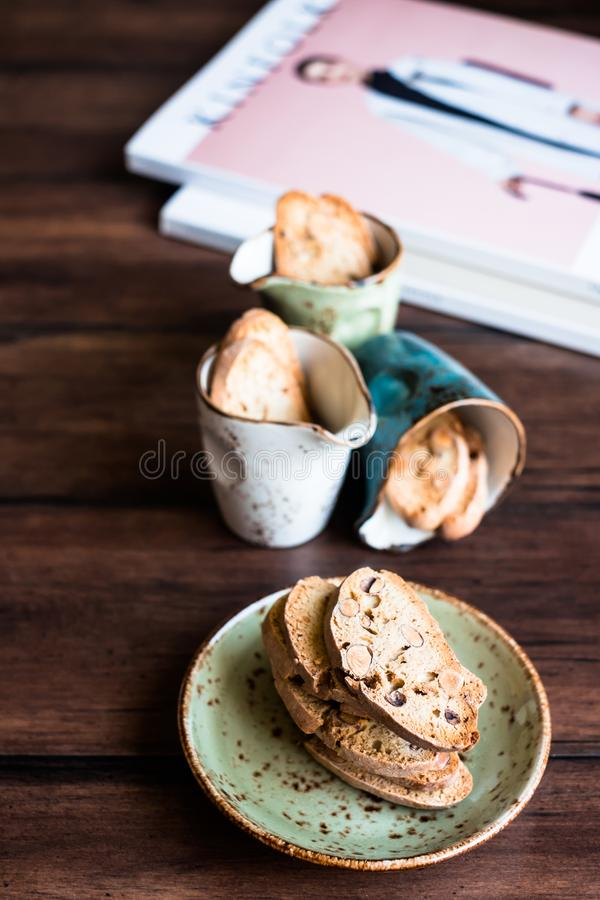 Italian dry cookies cantucci or biscotti with almond nuts stacked on a dessert plate on a wooden table, selective focus. Image wit stock images