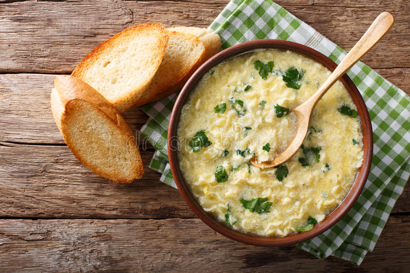 Italian egg soup stracciatella with farfalline pasta and parmesan close-up. horizontal top view royalty free stock images