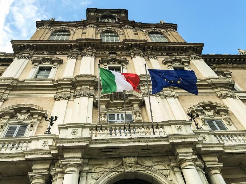 Italian and european flags on the facade of government palace vawing in the wind stock photos