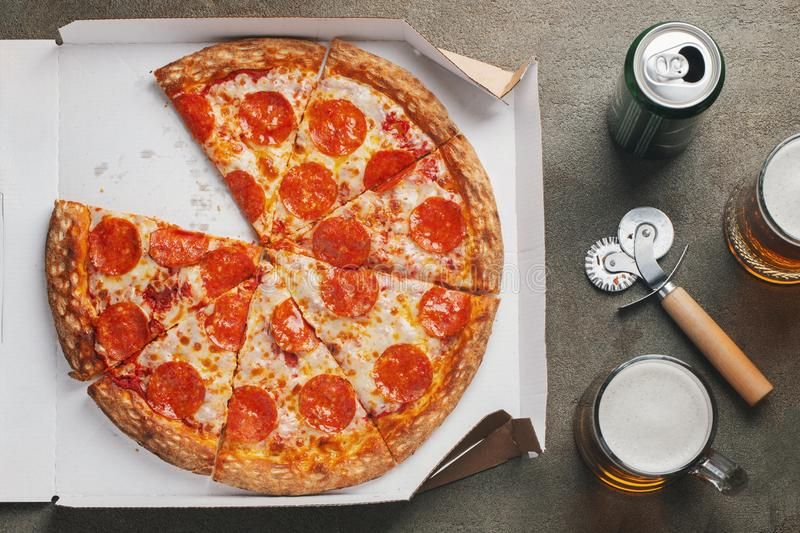 Italian fast food. Delicious hot pepperoni pizza in a box, and glass of beer sliced and served on brown table, close up view. royalty free stock images