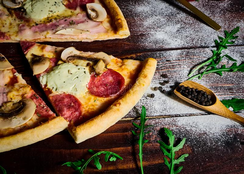 Italian fast food. Delicious hot pizza sliced and served on wooden platter with ingredients, close up view. Menu photo.  royalty free stock image