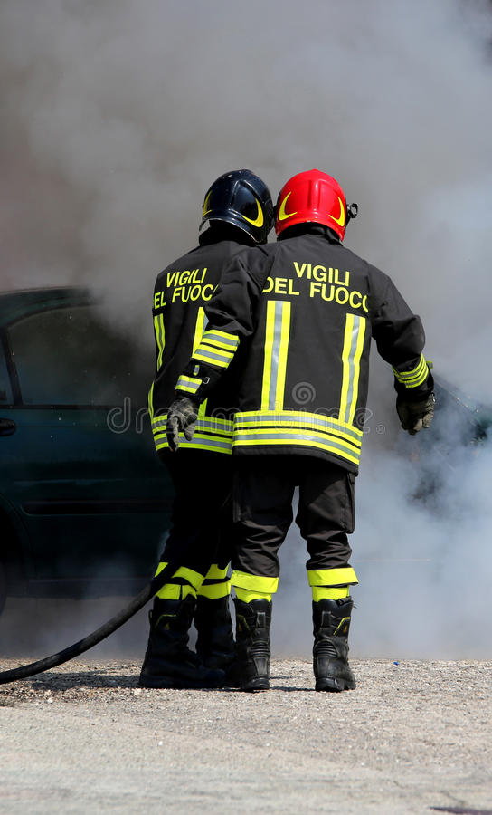 Italian fire brigade with the letter on the uniform meaning fire. Two Italian fire brigade with the letter on the uniform meaning firemen turn off the fire of stock photos