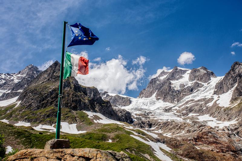 The Italian flag and the EU flag against the backdround of the mountains in the Alps. And blue sky with clouds stock photography