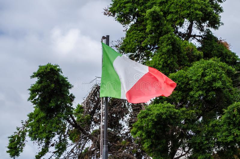 The Italian flag flying. In front of trees with its characteristic white, green and red colors stock photo