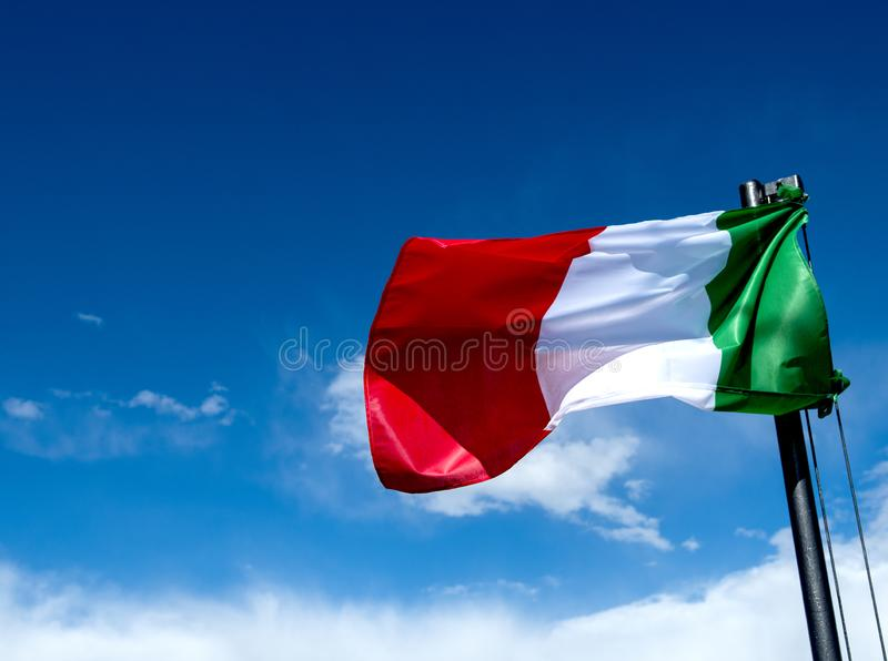 Italian Flag Green White and Red waving in a blue sky with clouds. A Italian flag waving in the sky with clouds,in a blu sky and gives thougt of pride stock images
