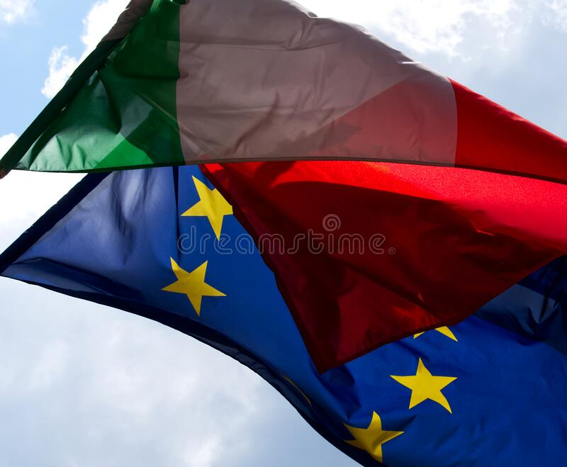 Italian flag waves over European Union flag. stock image