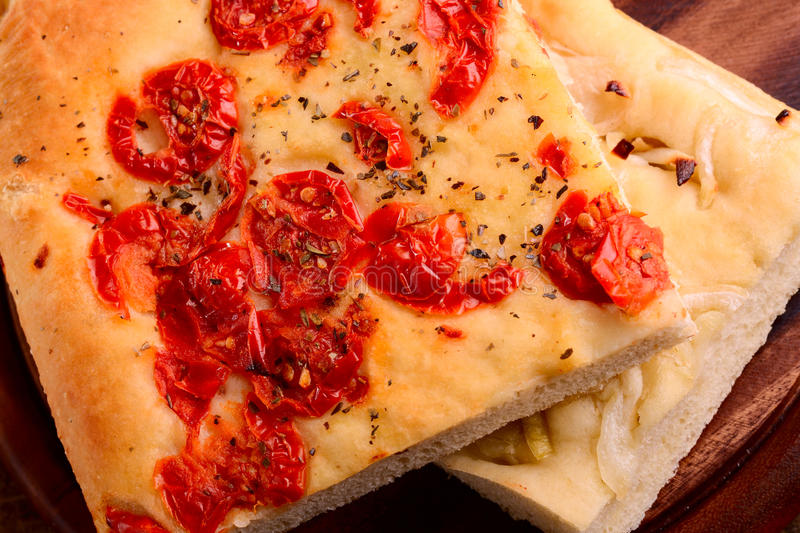 Italian focaccia with little tomatoes and with onions stock images