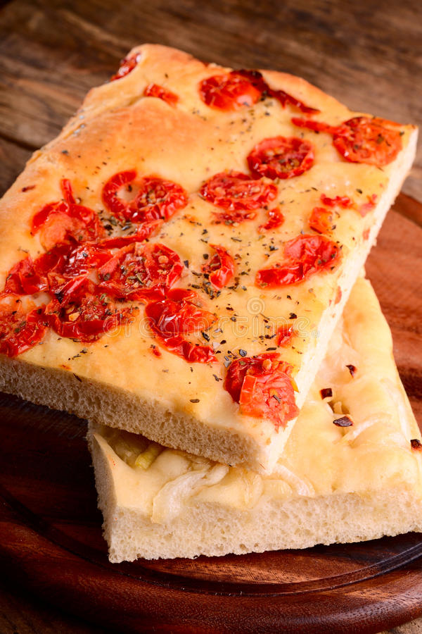 Italian focaccia with little tomatoes and with onions stock photo