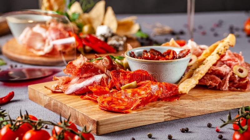 Italian food. Assortment of appetizers for a large company in a restaurant. Different types of smoked meat, sausages and cheeses royalty free stock image